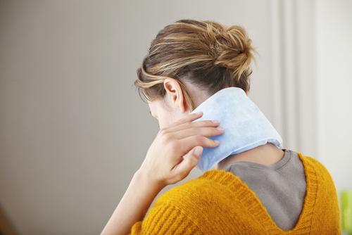 woman uses a cold compress on her neck