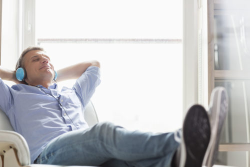 man relaxes in a reclined chair while listening to music