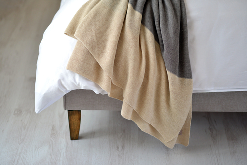 A neutral color throw is draped across white bedding